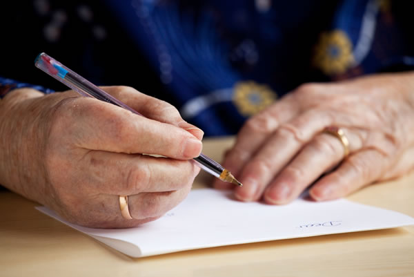 A person is writing a letter with pen and paper